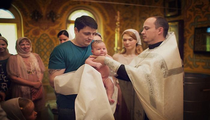 Крестный держит грудничка